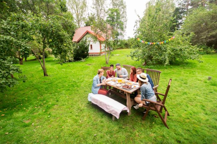 Familj sitter vid dukat träbord i trädgården. I Bakgrundens syns en vit villa.