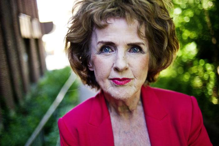 Porträtt på journalisten Elisabet Höglund klädd i röd kavaj.