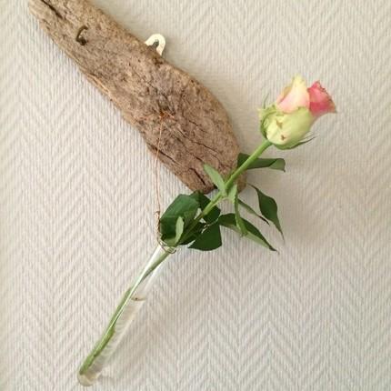 En enkel ros i en provrörsvas fäst på ett strandfynd.