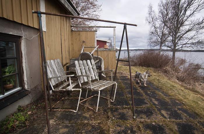 En vädringsställning , som har vädrat sig hela vintern, trasiga trädgårdsmöbler och oklippt gräs. Ingen uteplats att sitta och njuta vid precis. Jag skådar hellre ut mot sjön, än att se eländet.