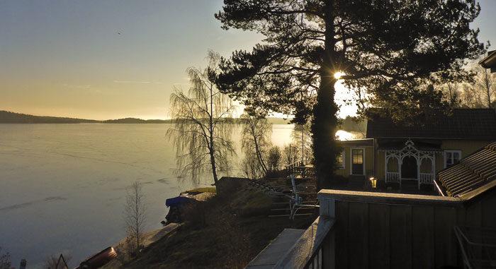 Det här är vad min husse kan se. Visserligen skymmer tallen solen så här års, men man kan ju ana den. Det är fortfarande is på sjön.