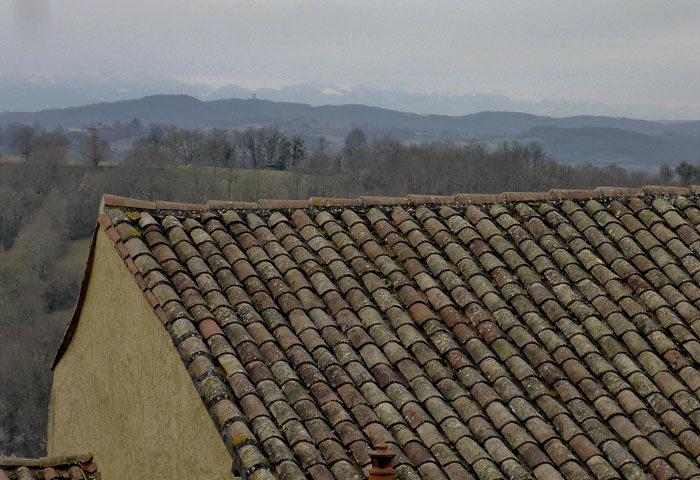 Tittar man söderut från samma slott i samma Aurgnac, så ser man berg. Det är Pyrenéerna som har placerat sig där. Fast det var lite disigt, när min husse tog bilden. Det kommer det nog inte vara när jag är där. Man ser tak också.